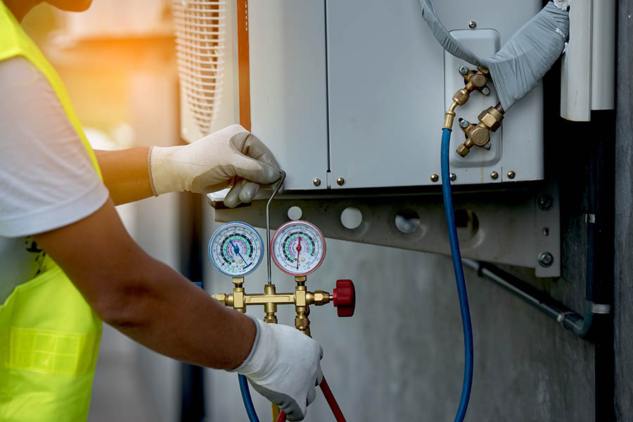 HVAC Contractor Insurance - Worker Fixing a Broken Air Conditioning Unit of a Business