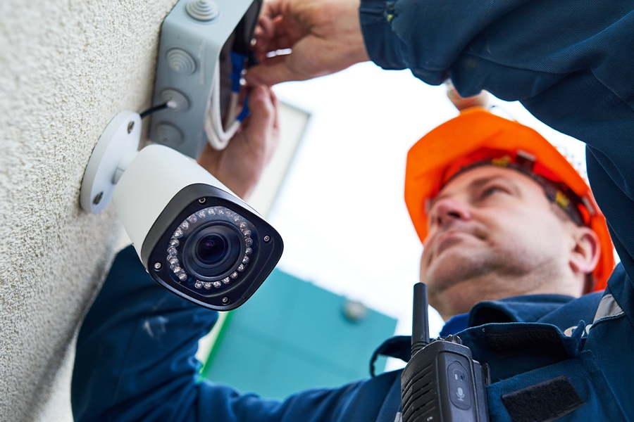 Alarm Contractor Insurance - Alarm Technician Worker Installing Video Surveillance Camera on a Wall