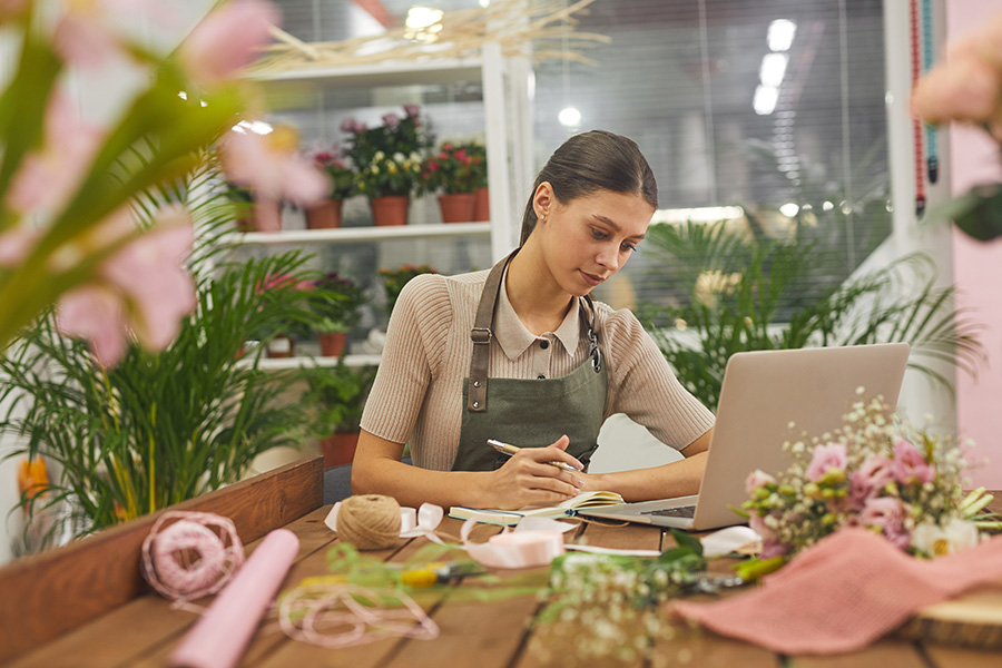 Business Insurance - Female Small Business Owner Managing Accounting Books While Using Laptop at Table in Flower Shop